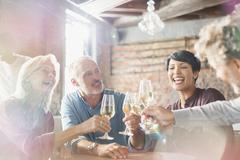 Friends toasting white wine glasses at restaurant table Stock Photos