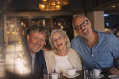 Portrait laughing friends drinking coffee in restaurant Stock Photos