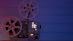 Film Projector over wooden table with red-blue light, with light beam Stock Footage
