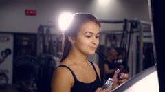 Fitness sporty girl drinking a water running on a treadmill in a gym Stock Footage