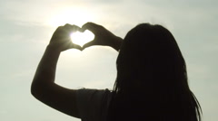 Woman shapes heart with hands over sun on sunset, Slow motion Stock Footage