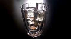 Pouring glass of beer with ice cubes in slow motion at 120fps in dark Stock Footage