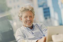 Portrait smiling businessman using digital tablet at sidewalk cafe Stock Photos