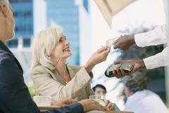 Businesswoman paying waiter with credit card reader at urban sidewalk cafe Stock Photos
