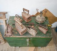 Ancient irons on a timber floor Stock Photos