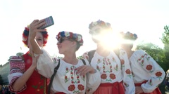 Young girls in wreaths and embroidery, national costumes make selfie on mobile Stock Footage