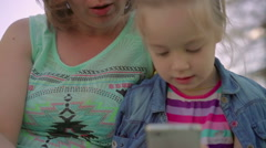 Mother helps daughter play a game on your phone Stock Footage