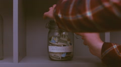 Caucasian male putting money into glass jar with his savings for future travels Stock Footage