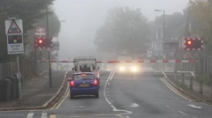A level crossing at Motspur Park, UK, foggy day. Stock Footage