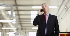 4K Serious mature businessman in factory negotiating a difficult deal over phone Stock Footage