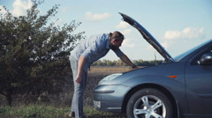 Man in blue jeans having automobile problems Stock Footage