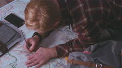 Caucasian male hiker preparing for a trip, studying a map on a wooden table Stock Footage
