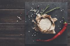 Cheese delikatessen with chili on black stone, brie camembert Stock Photos