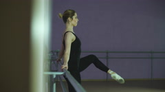 Athlete stretches herself near barre in the classroom Stock Footage