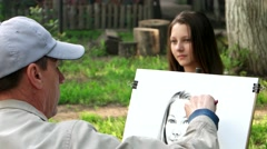 Artist paints on canvas portrait of a young girl, a street artist working in a Stock Footage