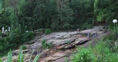 Caucasion women talking at mountain jungle waterfall Stock Footage