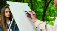 Artist draws a pencil on canvas portrait, a young girl posing street artist Stock Footage