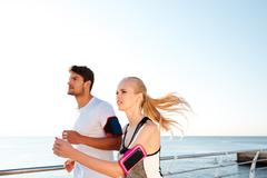 Young sports athletes couple sprinting as part of healthy lifestyle Stock Photos