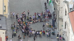 Clown performing on street, crowd of people enjoying show in European city Stock Footage