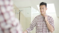 4K Cheerful young Asian man getting dressed & looking in mirror Stock Footage