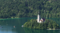 Small island with buildings on Bled lake in Slovenia, amazing landscape, tourism Stock Footage