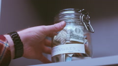 RL DOLLY Caucasian male putting a glass jar with his savings for future travels Stock Footage