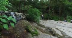 Women talking at mountain jungle waterfall Stock Footage