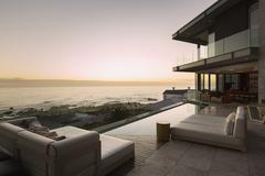Tranquil sunset ocean view beyond modern luxury home showcase patio Stock Photos
