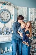 Family standing by the fireplace and Christmas tree. Stock Photos