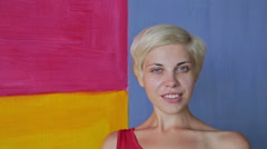 Pretty, young and blonde woman in red dress without make-up looking at camera Stock Footage