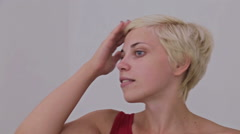 Pretty, young and blonde woman in red dress without make-up fixing hair Stock Footage