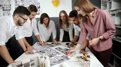 Four architects standing and planning around a table while looking down at Stock Footage