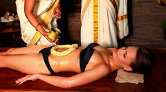 Woman having Indian stomach exotic treatment spa using pouring oil of dough. Stock Footage