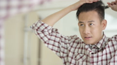 4K Cheerful young Asian man combing his hair & looking in mirror Stock Footage
