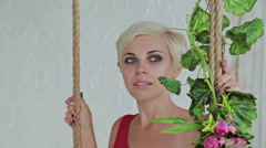 Pretty, young and sensual woman in red dress on a swing decorated with flowers Stock Footage