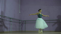 Ballerina making a jump in a dance hall. She is wearing the leotard with white Stock Footage