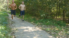 Two muscular athletes running at the forest path. Friends exercising together Stock Footage