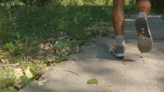 Feet of strong man running at the forest path. Male legs jogging during workout Stock Footage