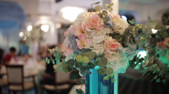 Beautiful bouquet of flowers in a vase. The high glass vase on the table Stock Footage