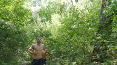 Group of young muscular athletes running at the forest path. Healthy lifestyle Stock Footage