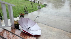 Raining falling on the ground with red umbrella Stock Footage