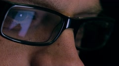 Eyes of serious young man in black rim glasses using his tablet computer. Screen Stock Footage