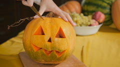 Girl carves chilling lantern on Halloween Stock Footage