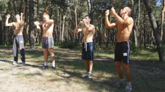Group of athletes warming up his body and hands before training in the forest Stock Footage