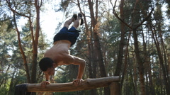 Muscular male fitness guy doing stunts on log at the wood. Athlete training Stock Footage