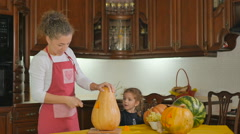 Small pretty girl eating a pumpkin on the kitchen Stock Footage