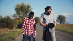 Two guys left broken car and hitchhiking Stock Footage
