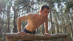 Athletic man doing push ups from log at the forest. Close up Stock Footage