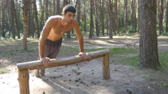 Strong young muscular guy training outdoor at the wood in summer Stock Footage
