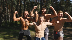 Group of naked strong muscular man posing and shows his muscles at the forest Stock Footage
